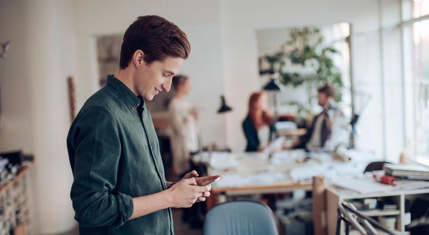 Mann sjekker telefon på kontoret
