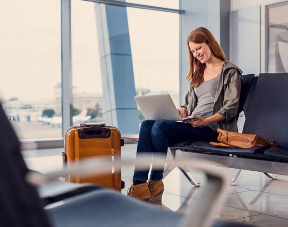 Dame med PC på flyplass