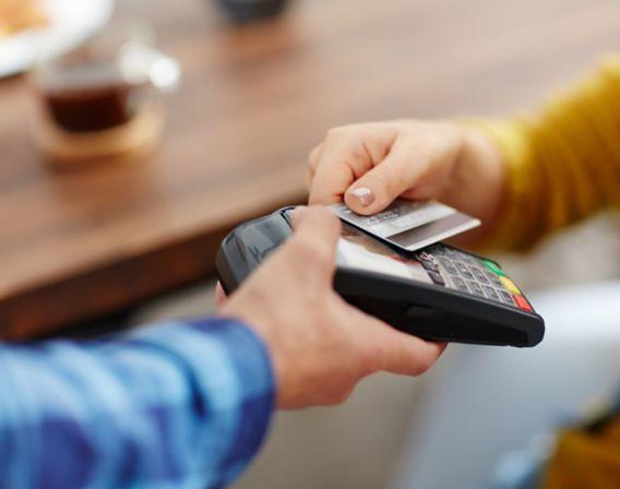 Dame betaler med kort på en betalingsterminal