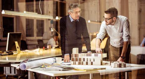 Bilde av ung arkitekt som diskuterer med eldre arkitekt
