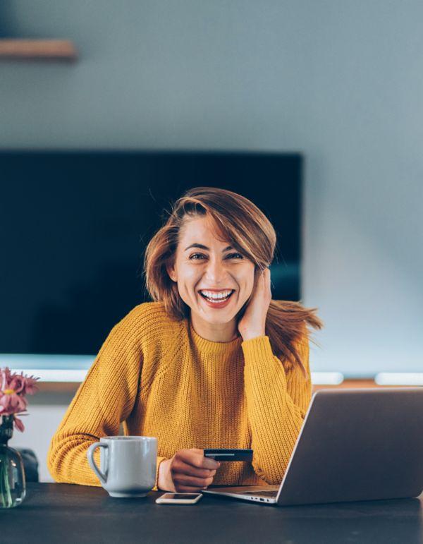 Kvinne som sitter ved pc og smiler