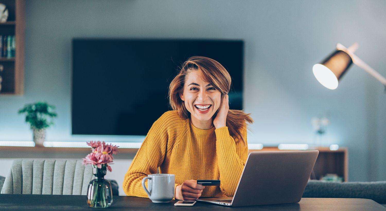 Bilde av smilende kvinne som sitter på hjemmekontor