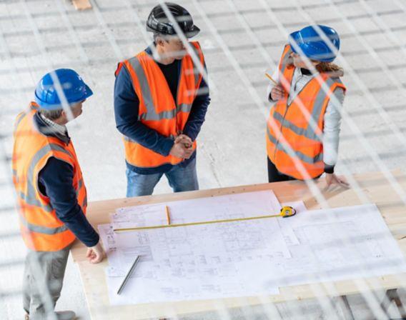 Byggarbeidere ser på tegninger