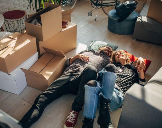 Kvinne og mann ligger på gulvet med flytteesker