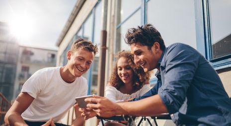 Bilde av tre unge mennesker som ser på en mobil og smiler