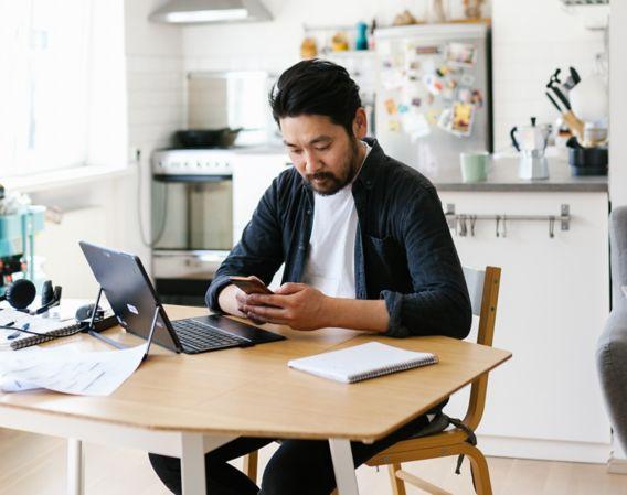 Mann sitter ved kjøkkenbord med pc på bordet og ser på mobil