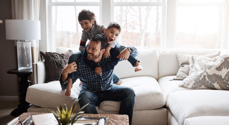 Far med to sønner sitter i sofa