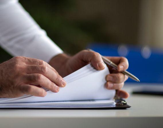 En mann som blar gjennom en bunke med dokumenter