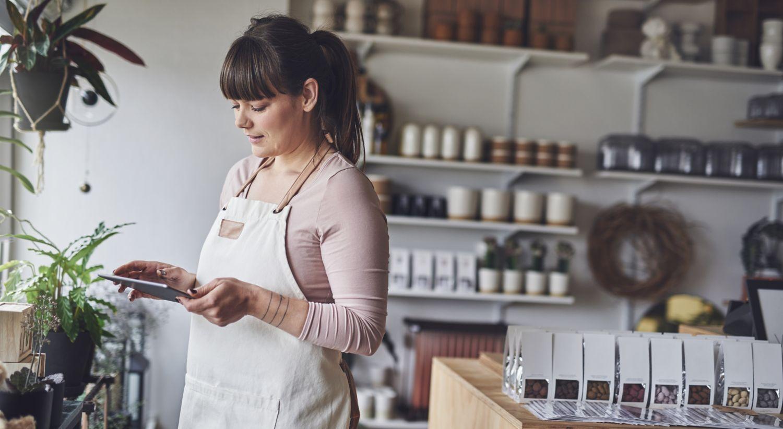 Bilde av en kvinne på jobb som ser på en Ipad