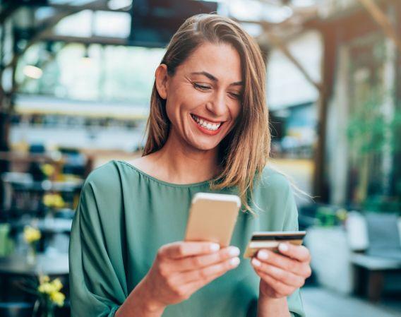 Dame som smiler mens hun holder en telefon og et bankkort
