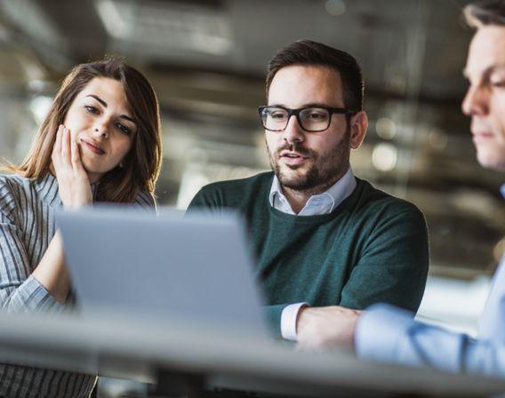 Tre kollegaer som sitter og vurderer et bedriftslån foran en laptop