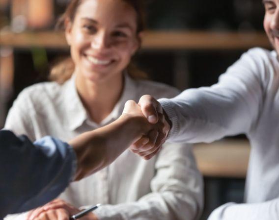 Forretningsmøte der to mennesker inngår en avtale