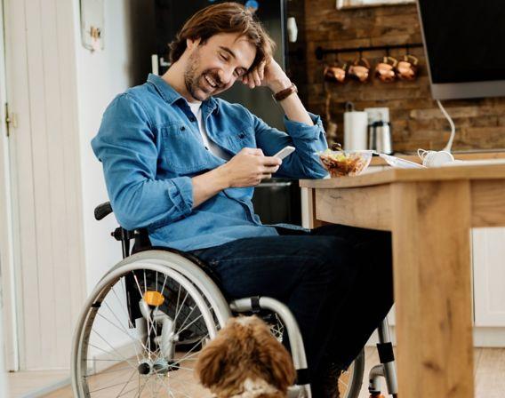 Mann som sitter i rullestol og smiler